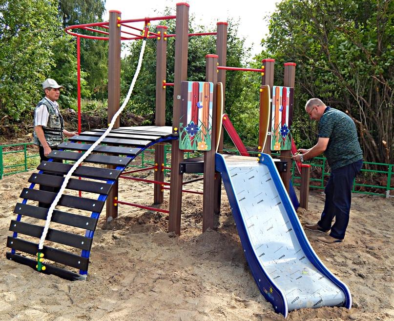 А.Н.Мосунов (справа) проверяет верность установки подрядчиком элементов детской площадки.